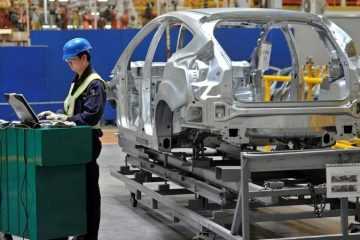 An employee uses a laptop next to a car body at an assembly line at a Ford manufacturing plant in Chongqing municipality April 20, 2012.    REUTERS/Stringer  CHINA OUT. NO COMMERCIAL OR EDITORIAL SALES IN CHINA - RC14E37FAA00